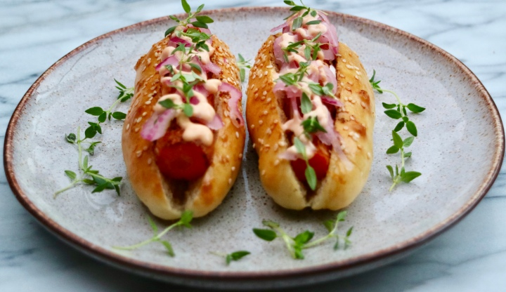 Vegetarian roasted hot dog with Sriracha mayo and pickled onion