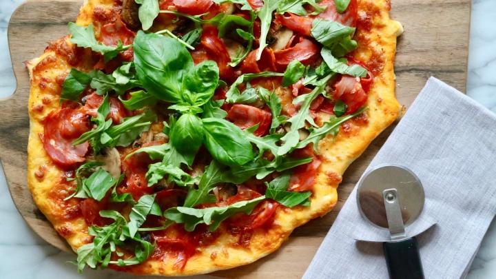 Pizza with salami, roasted mushrooms andarugula