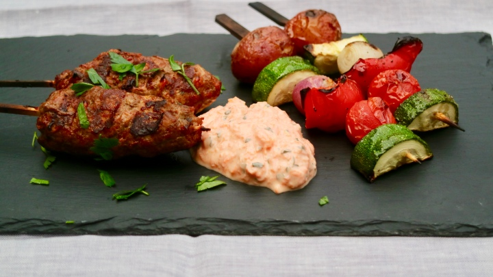 Grilled beef and vegetable skewers with carrot tzatziki and parsley